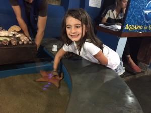Olivia fazendo carinho em uma estrela do mar