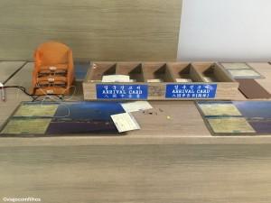 Detalhe da mesinha com os formulários de entrada na Coreia. Óculos para quem precisar, canetas, ...
