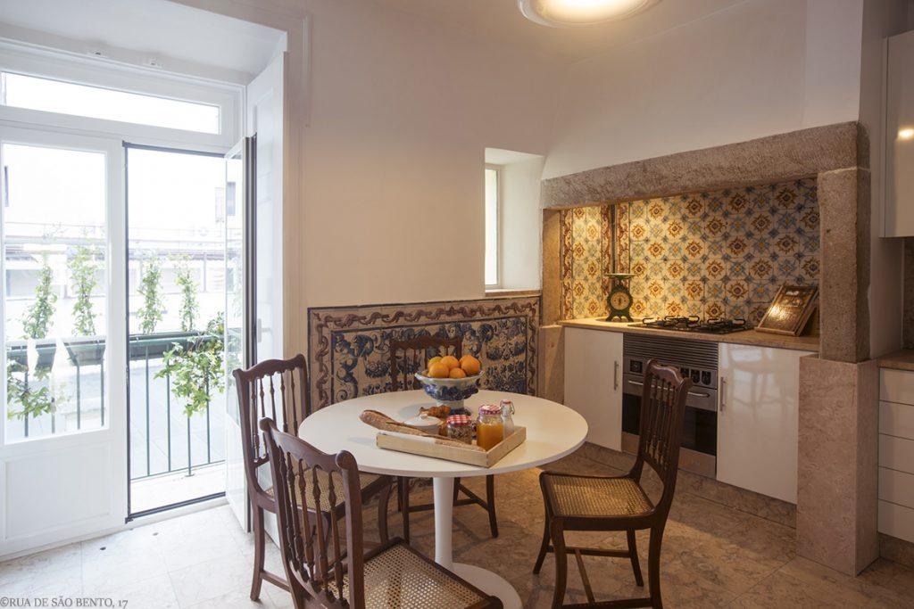 Cozinha com mesa quatro cadeiras e azuleijos portugueses