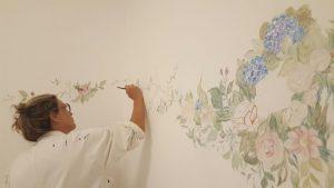 Mulher pintando mural na parede