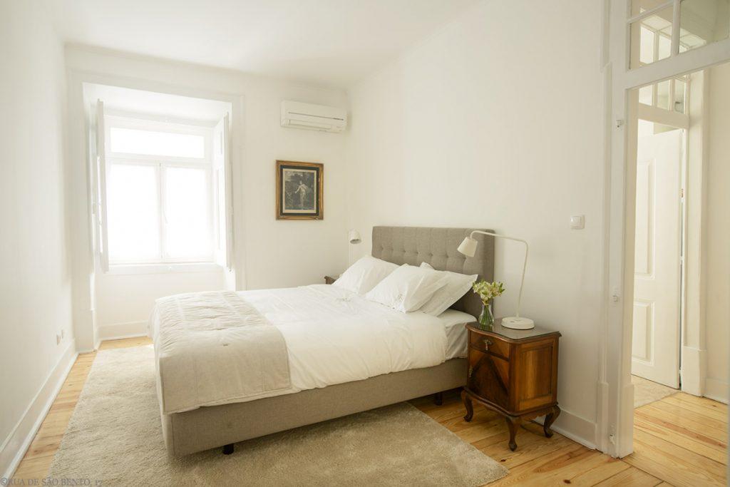 Quarto com cama de casal duas mesas de cabeceira e janela