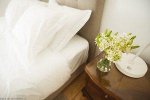 Mesa de cabeceira com flores brancas